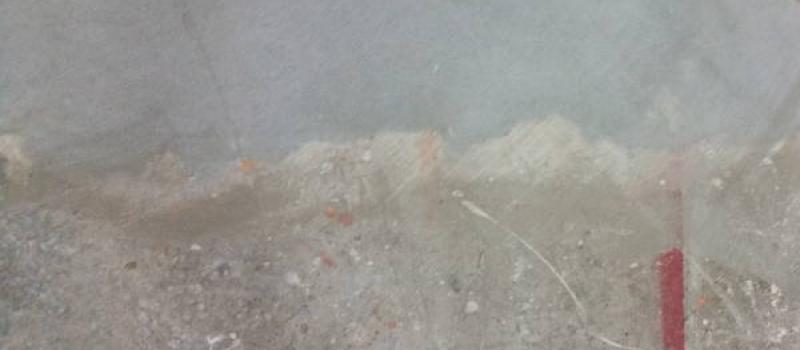 Een licht vervuilde betonvloer, niet met lijmresten maar met diverse verfresten, die gedeeltelijk is schoongeschuurd middels diamant schuren