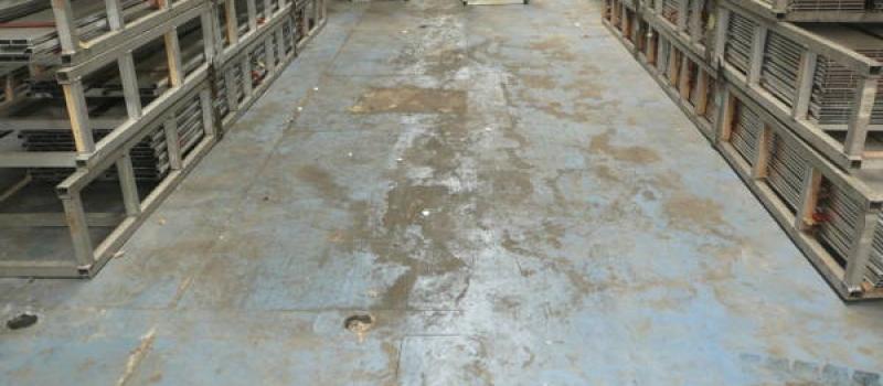 Een afbeelding van een vloer met een oude coating waarbij de betonvloer en de coating zwaar zijn beschadigd