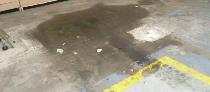 Een derde afbeelding van een sterk vervuilde betonvloer voorafgaand aan de behandeling door Moru.